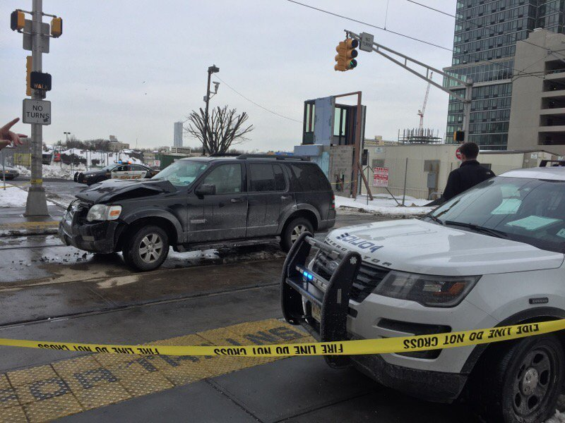 Car slides on city road   and then into light rail train in Jersey